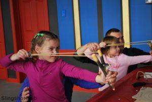 родители и дети соревнуются в стрельбе из рогатки