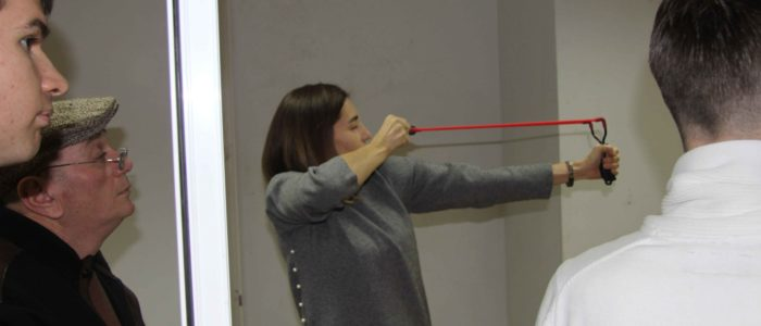 молодая девушка стреляет из рогатки