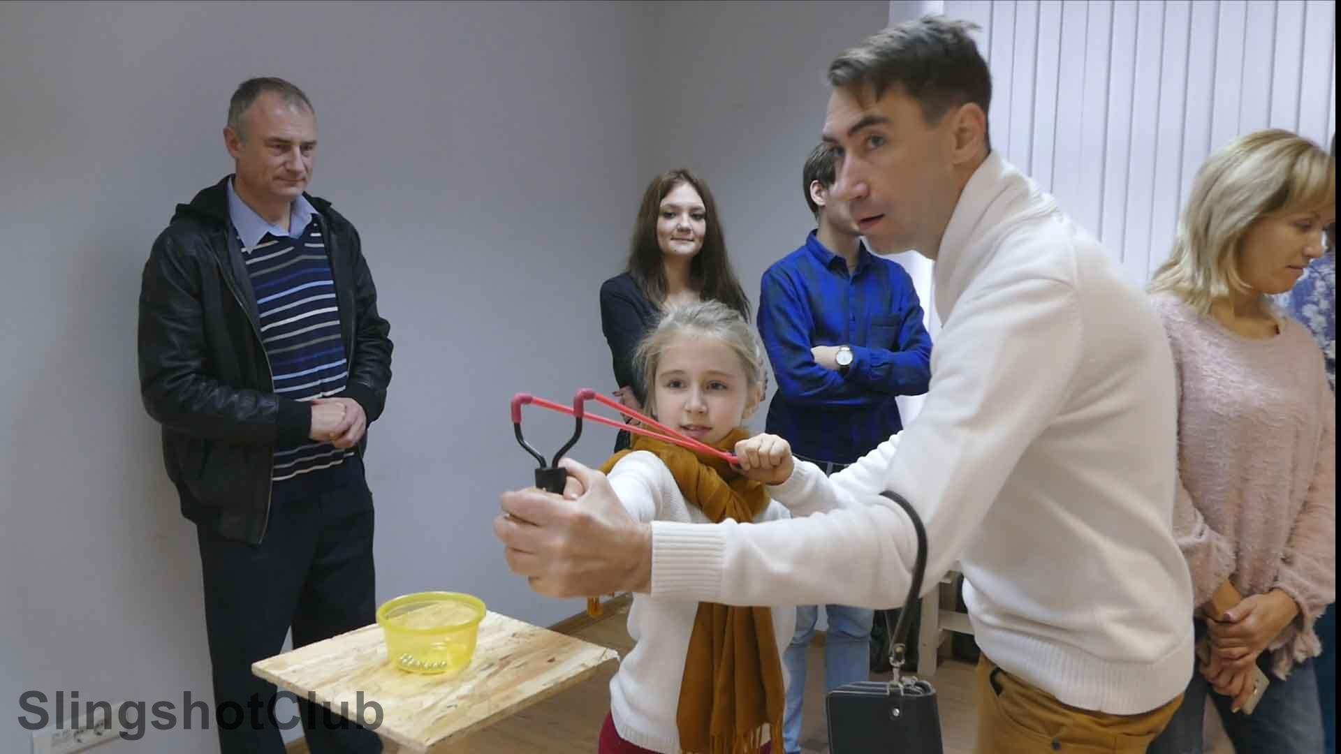 папа учит дочку стрелять из рогатки